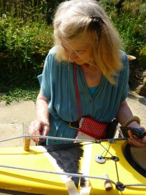 Christina Bonnett painting a kayak